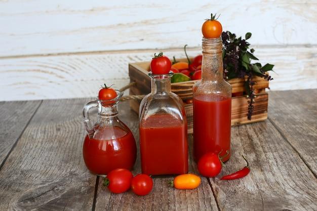 メガネと木製の背景に木製のテーブルの上のトマトのトマトジュース