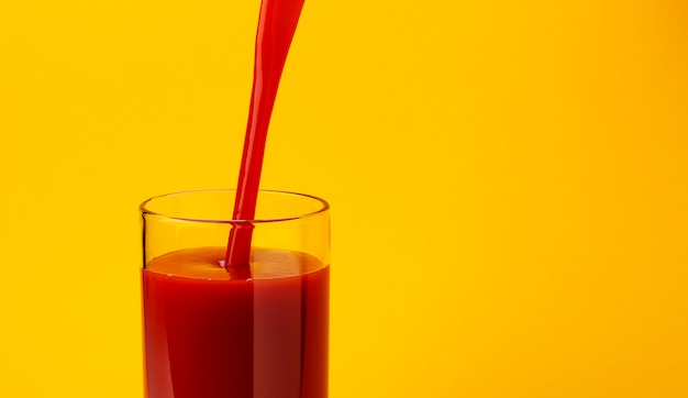 Tomato juice pouring into glass, isolated on yellow