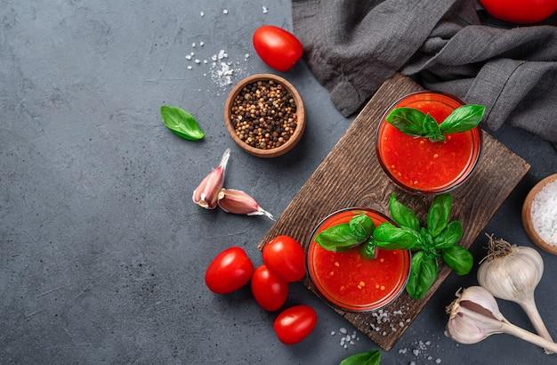 Tomato juice spices basil salt and garlic on a grayblue background