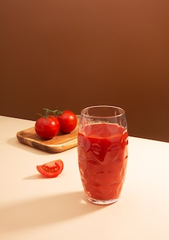 Tomato juice and two tomatoes on the table
