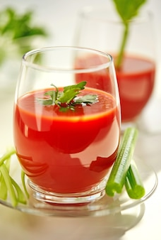 Tomato juice on a white plate with a garnish of celery and parsley. healthy eating concept