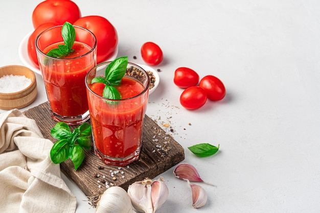 Tomato juice with basil and spices on a light background side view space for copying