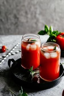 灰色の背景にガラスの氷とトマトジュース