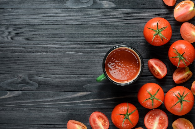 Tomato juice with tomatos on black wooden table top wiew