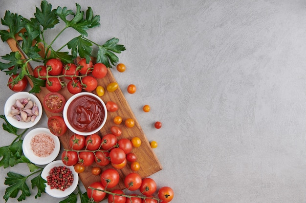 Salsa di ketchup di pomodoro in una ciotola con spezie, erbe aromatiche e pomodorini