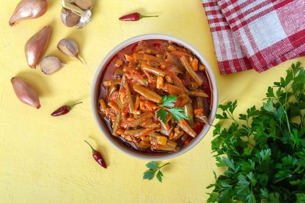 그릇에 녹색 콩 꼬투리의 토마토 lobio