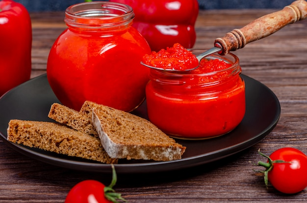 Tomato mousse in glass jars in a black plate on a rustic wooden table