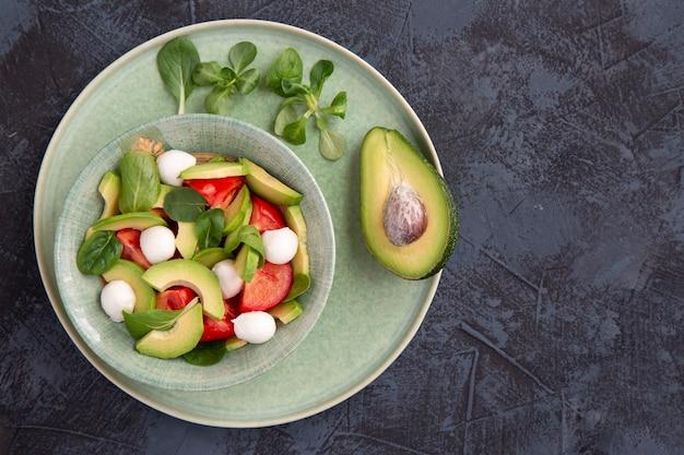 Салат из помидоров, моцарелла, авокадо и базилика на темном фоне стола здоровое питание вегетарианская еда