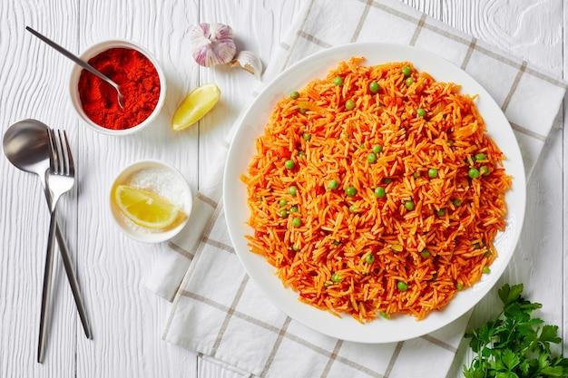 토마토 양파 녹색 완두콩 쌀 필라프, 레몬 웨지와 신선한 고수 잎이있는 흰색 나무 테이블에 흰색 접시에 tamatar biryani, 위에서 가로보기, 평면 누워, 클로즈업