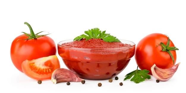 ガラスプレートのトマトペースト、トマト、ニンニク、コショウのクローズアップ