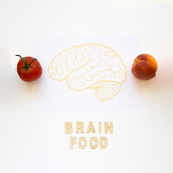Tomato and peach near brain food words with drawing on paper