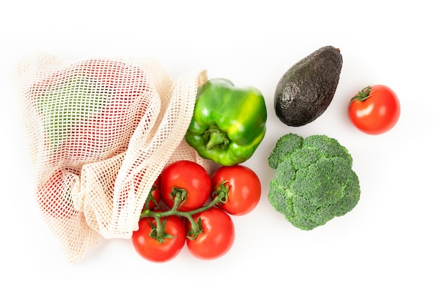 白地に再利用可能な環境にやさしいバッグに入ったトマト、コショウ、アボカド、ブロッコリー。持続可能なライフスタイル。プラスチックのない食品の買い物。ゼロウェイストのコンセプト。