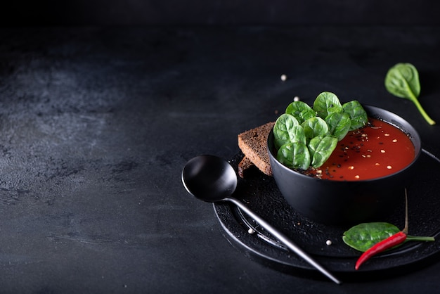 Tomato puree soup with spinach in a black bowl, close-up