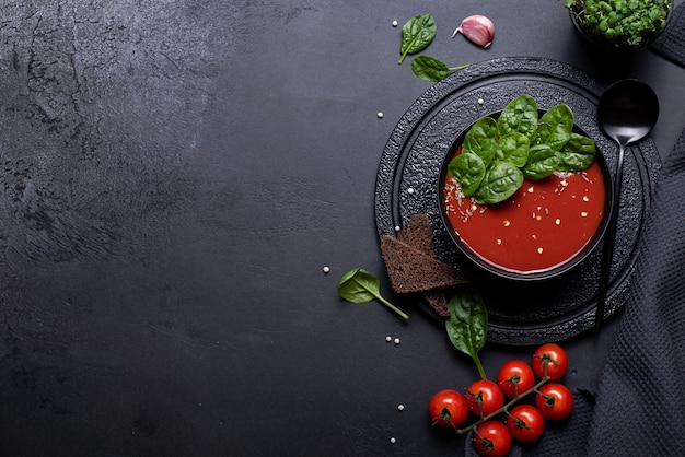Tomato puree soup with spinach in a black bowl, top view