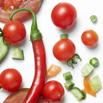 Tomato and red hot chili peppers isolated on white surface