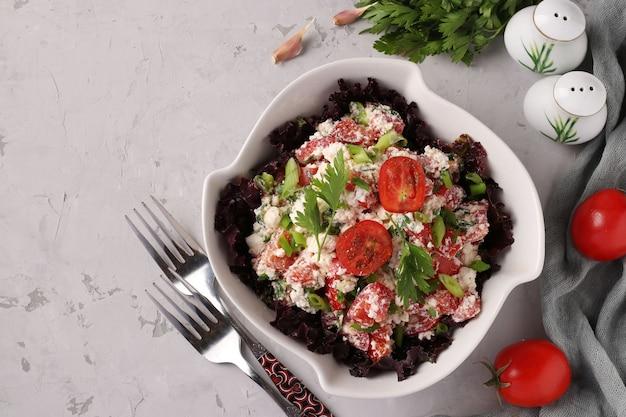 カッテージチーズ、ネギ、パセリ、スパイスのトマトサラダ、灰色の表面の白いボウル、上面図、テキスト用スペース