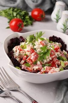 밝은 회색 배경에 흰색 그릇에 코티지 치즈, 파, 파슬리, 향신료를 넣은 토마토 샐러드