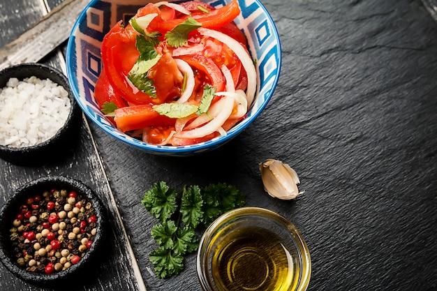 Томатный салат с луком и кинзой на черном фоне, вид сверху. концепция восточной кухни