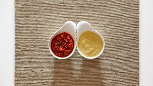 플레이스 매트에 세라믹 그릇에 토마토 소스와 겨자. 전통 패스트 푸드와 바베큐 소스.