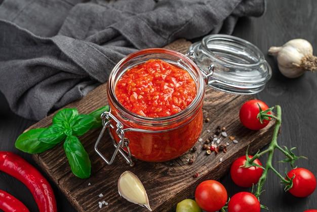 材料の背景にガラスの瓶にトマトソース。イタリアのマリナーラソース。側面図、クローズアップ。