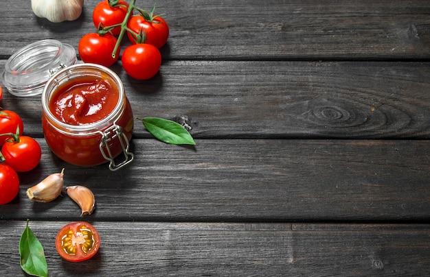 Томатный соус в стеклянной банке с лавровым листом и вишней на деревянном столе