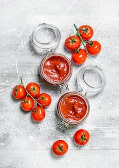 지점에 체리 토마토와 함께 항아리에 토마토 소스. 흰색 시골 풍 테이블에