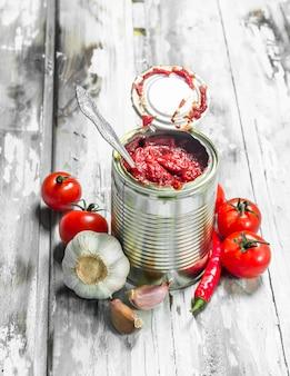 숟가락, 마늘, 후추와 함께 깡통에 토마토 소스. 나무 배경