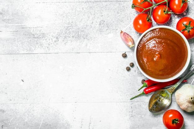 소박한 테이블에 숟가락, 마늘, 체리와 그릇에 토마토 소스