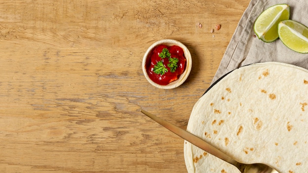 Tomato sauce near spoon and tortilla with sliced lime