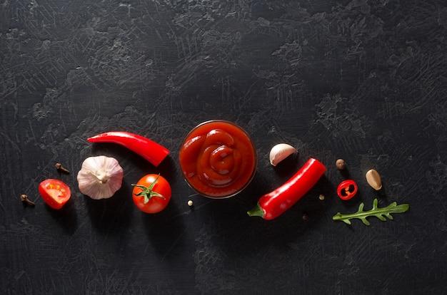 Томатный соус на черном фоне текстуры