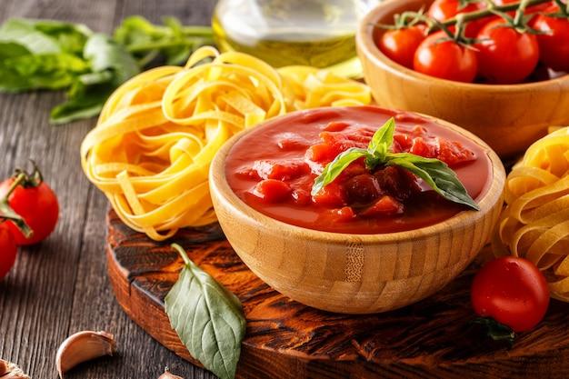 Томатный соус, паста, помидоры, чеснок, оливковое масло на старых деревянных.