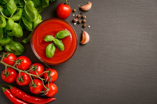 Tomato sauce with ingredients on black background, top view, flat lay, copy space.