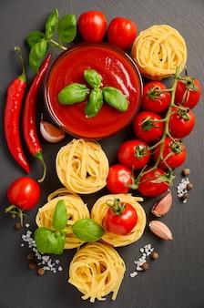 Tomato sauce with pasta on black background.