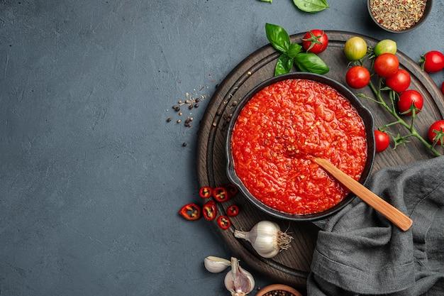 짙은 청회색 배경에 후추, 마늘, 바질을 넣은 토마토 소스. 파스타 드레싱, 피자 소스. 상위 뷰, 복사 공간