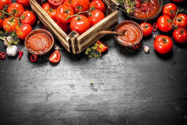 향신료, 고추, 마늘을 곁들인 토마토 소스. 검은 칠판에.
