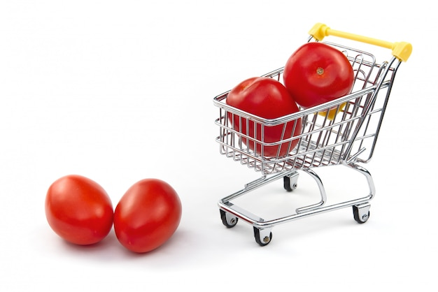 A tomato in shopping cart isolated on white background. ripe tasty red tomatos in shopping cart. tomato trading concept. online shopping concept. cart and tomato over a white background.
