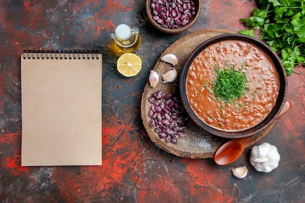 Cucchiaio di aglio di fagioli di sapone di pomodoro sul tagliere di legno e bottiglia di olio verde limone accanto al taccuino