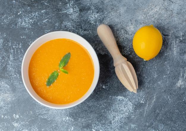 토마토 수프와 레몬 압착기를 곁들인 신선한 레몬.