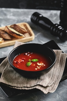 Tomato soup in a black bowl on a gray stone background. view from above. copy space. gray background. calm light. food concept.