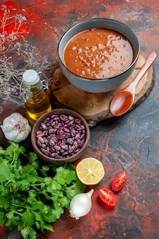 Zuppa di pomodoro in una ciotola blu su una bottiglia di olio di fagioli vassoio di legno sulla tabella di colori misti