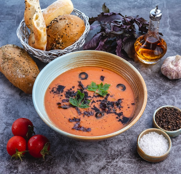 Tomato soup bowl garnished with olive dark basil leaves and parsley