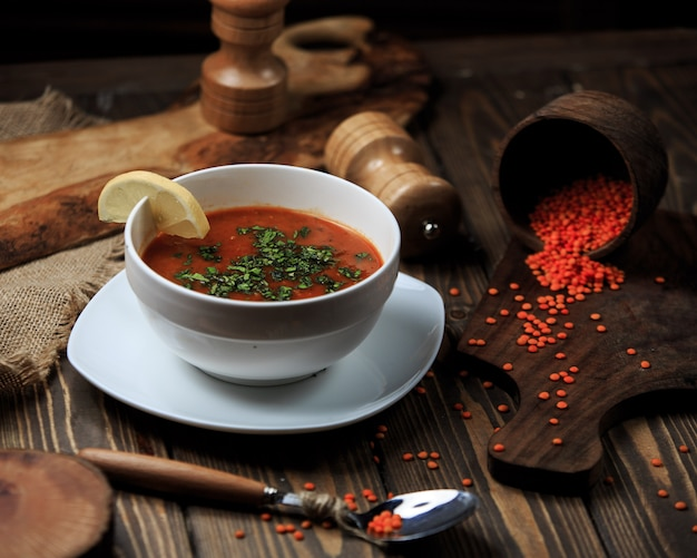 Tomato soup in a bowl with lemon and spices