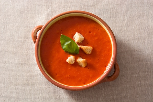 Tomato soup in brown bowl garnished with croutons top view