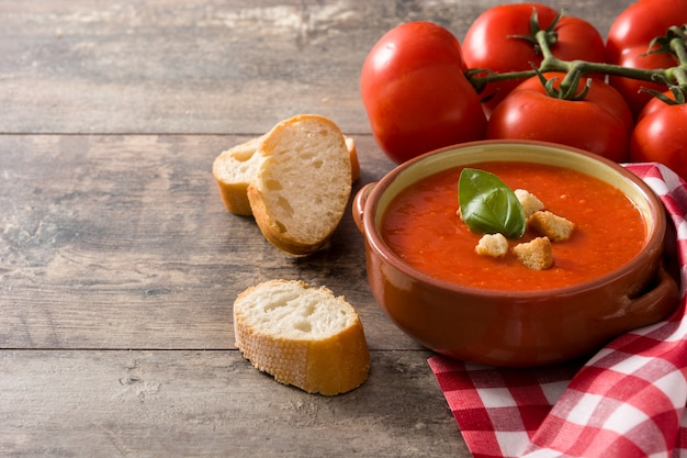 Tomato soup in brown bowl on wooden table copy space
