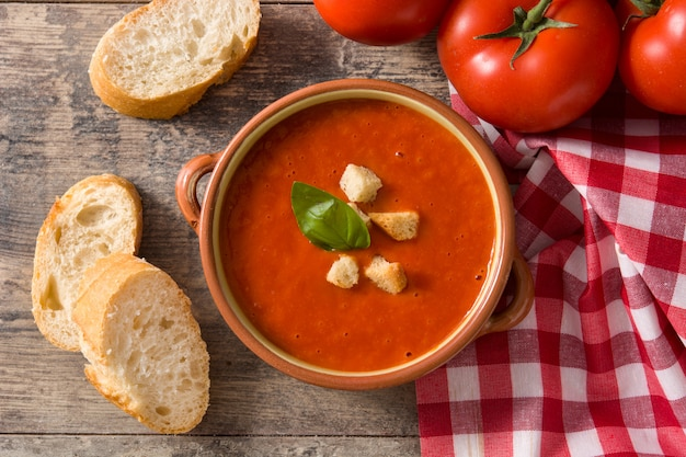 Tomato soup in brown bowl on wooden table. top view