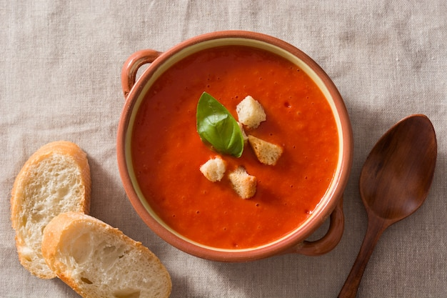 Tomato soup in brown bowl on wooden table top view