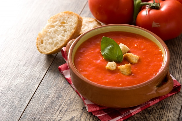 Tomato soup in brown bowl on wooden table