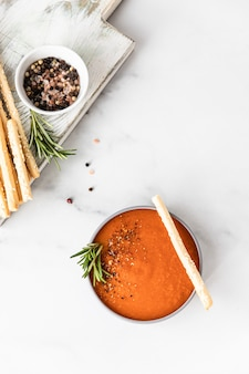 Tomato soup garnish with ground pepper rosemary and bread sticks light background