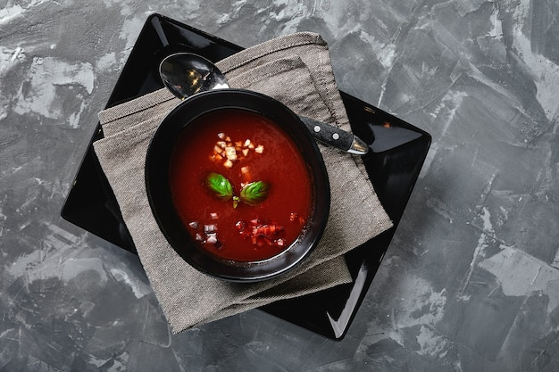灰色の石の上の黒いボウルにトマトスープ上からの眺め