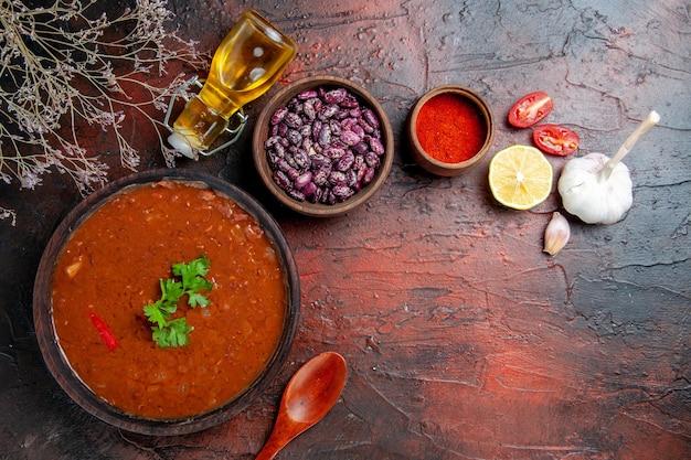 混合色のテーブルに茶色のボウルペッパーガーリックレモンと豆のトマトスープ